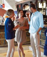 写真:女性2人と男性1人がバーで、お酒を飲みながら会話している様子